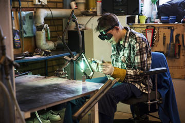 Young man welding metal at workshop