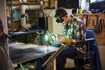 Sweden, Young man welding metal