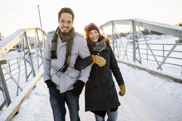 Smiling couple walking on snow covered bridge
