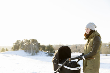 Sweden, Sodermanland, Jarna, Woman with baby stroller standing in snowy field