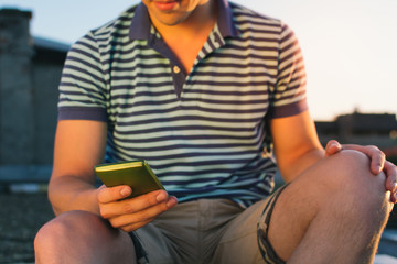 Young man sitting and using phone