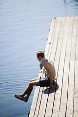 Sweden, Smaland, Loftahammar, Young man sitting on wooden jetty by lake