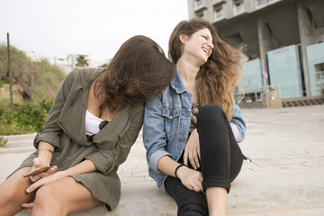 Israel, Tel Aviv, Laughing  young women sitting on steps