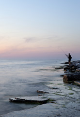 Sweden, Oland, Sandvik, Man fishing at sunset
