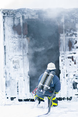 Firefighter kneeling in front of building covered with foam