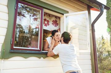 Sweden, Gastrikland, Sandviken, Couple kissing though window of house