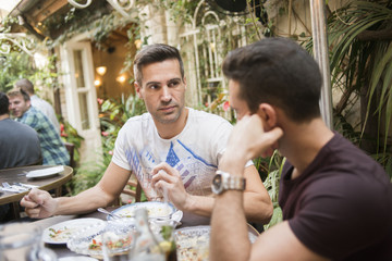 Israel, Tel Aviv, Gay couple having dinner in restaurant