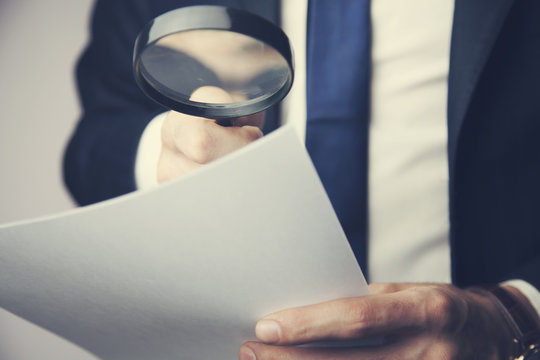 man hand magnifier and documents
