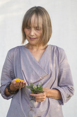 Sweden, Sodermanland, Jarna, Senior woman holding thyme herbs and petals