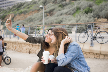 Israel, Tel Aviv, Two smiling women taking selfie