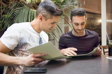 Israel, Tel Aviv, Homosexual couple looking at menu in cafe