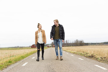 Sweden, Ostergotland, Mjolby, Teenage girl (14-15) and young man walking along country road