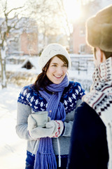 Sweden, Stockholm, Young woman wearing knit hat and gloves holding hot chocolate