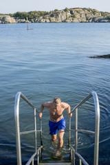 Sweden, Vastra Gotaland, Gothenburg, Saltholmen, Man coming up stairs from sea