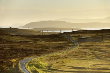 Power lines along road in landscape against sky