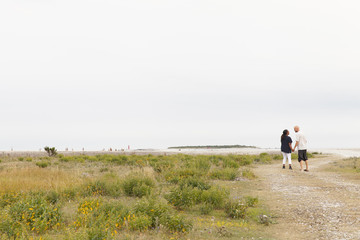 Sweden, Gotland, Furillen, Mid adult couple holding hands and walking along footpath