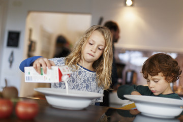Sweden, Girl (10-11) and boy (6-7) pouring milk into plate