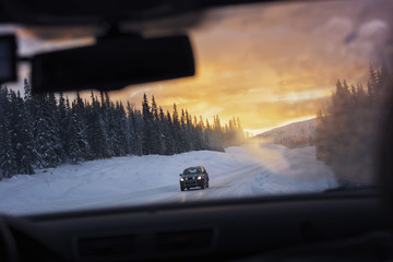 Car moving on snowy road seen through windshield