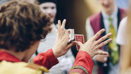 Sweden, Uppland, Hagaparken, Young circus performer showing card trick