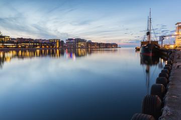 Sweden, Skane, Malmo, Moored ship and cityscape at dusk