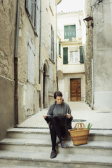 France, Languedoc-Roussillon, Sauve, Young tourist sitting on steps and looking at map