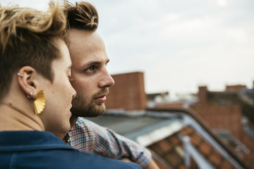 Germany, Berlin, Young couple side by side on rooftop against sky