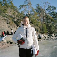 Sweden, Uppland, Varmdo, Bjorno, Portrait of mid adult woman holding ice skates