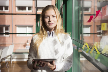 Sweden, Portrait of young businesswoman holding tablet pc