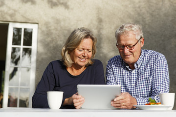 Smiling senior couple using digital tablet while sitting outdoors