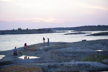 Sweden, Stockholms Skargard, Sodermanland, Varmdo, Villinge, People walking on rock along sea