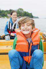 Sweden, Uppland, Runmaro, Barrskar, Portrait of boy (6-7) on motorboat, mother in background