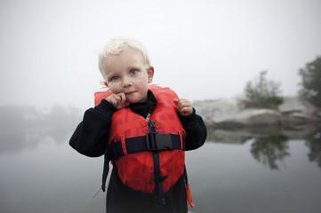 Sweden, Uppland, Vidinge, Portrait of boy (2-3) in lifebelt