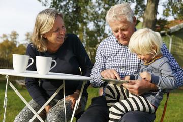 Sweden, Sodermanland, Senior couple sitting with grandson (2-3) at table using digital tablet