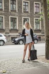 Denmark, Copenhagen, Teenage girl (14-15) standing on street holding bag and phone