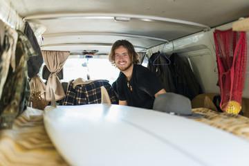 Australia, Queensland, Portrait of young surfer smiling inside car