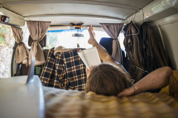 Australia, Queensland, Surfer reading book in car