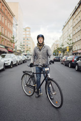 Sweden, Sodermanland, Stockholm, Sodermalm, Hornstull, Mid adult man standing by his bicycle on street