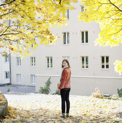 Finland, Helsinki, Kallio, Woman under maple trees, looking back