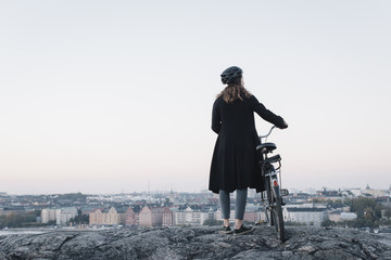 Sweden, Sodermanland, Stockholm, Sodermalm, Skinnarviksberget, Rear view of young woman standing by bicycle on rock