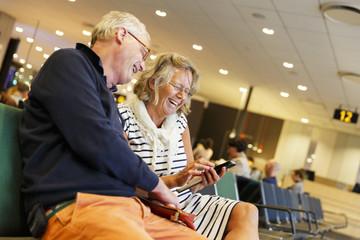 Sweden, Uppland, Senior couple using smartphone in airport
