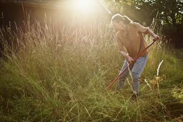 Female cutting grass in field