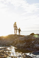 Sweden, Gotland, Faro, Rear view of mother and son (2-3) standing on rocky coast