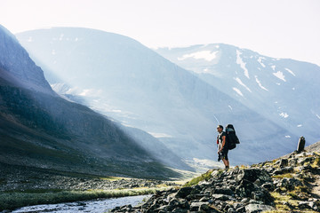 Sweden, Lapland, Ladtjovagge, Kungsleden, Male hiker standing by river in mountain valley