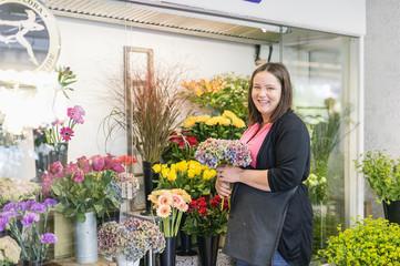 Sweden, Vastmanland, Portrait of florist holding bunch of flowers