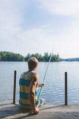 Finland, Pirkanmaa, Salmentaka, Lake Palkanevesi, Young man fishing off lake pier