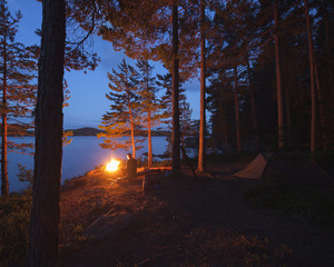 Sweden, Narke, Stora Trehorningen, Man by bonfire on riverbank
