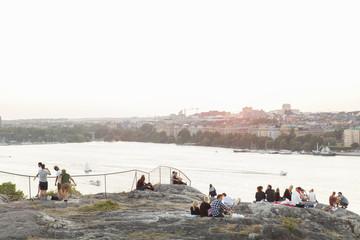 Sweden, Stockholm, Sodermalm, Skinnarviksberget, People relaxing on rocky riverbank