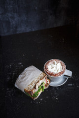 Cup of hot chocolate and sandwich in dark room