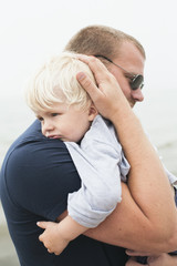 Sweden, Gotland, Ljugarn, Man embracing boy (2-3)