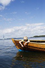 Sweden, Sodermanland, Stockholms Skargard, Dalaro, Boy (10-11) sitting in moored boat